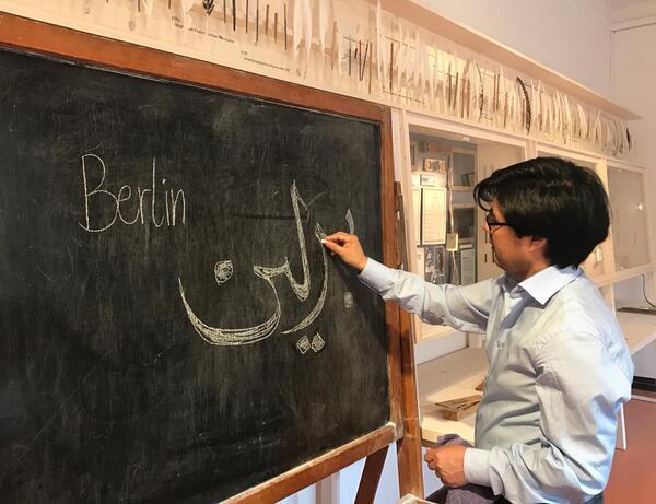 Ein afghanischer Kalligraph beim Schreiben an der historischen Berliner Schultafel | © Stadtmuseum Berlin | Foto: Vanessa Hoffmann