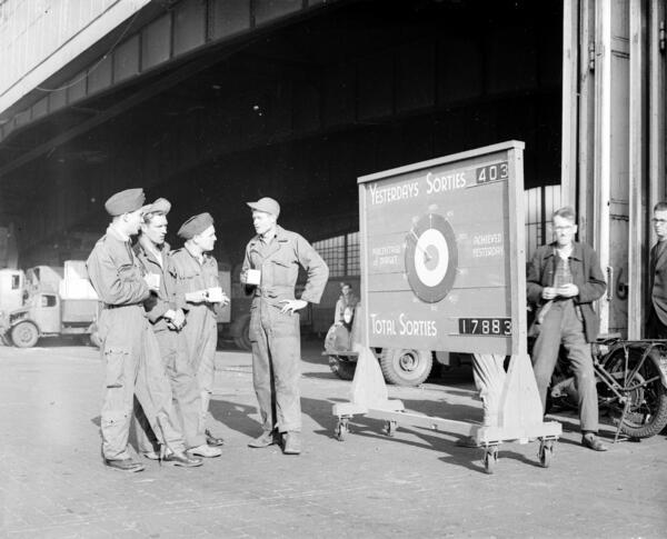 Vor dem Hangar 4 in Gatow befand sich eine Anzeigetafel mit dem aktuellen Stand der Luftbrücken-Tageslieferungen (Sorties). Ihre Gesamtzahl hatte sich im August 1948 bereits auf annähernd 18000 summiert. | Crown copyright 1948, reproduced under the terms of the Open Government Licence, published as a courtesy of Air Historical Branch, RAF (GAT R-1852)